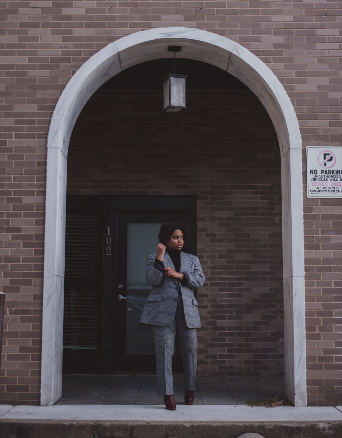 woman standing in blue suit in entry way